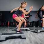 45884821 - athletic woman trainer doing aerobic class with steppers to people group on a fitness center. sport and health concept.